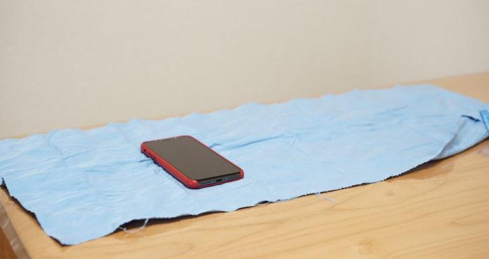 Mont-bell モンベルのマイクロタオルフェイスを広げた状態。iPhone Xと比較