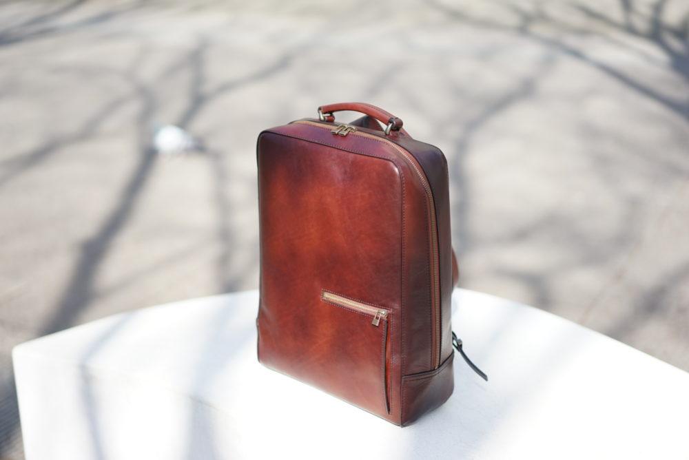 陽の光のもとで輝く antique square backpack